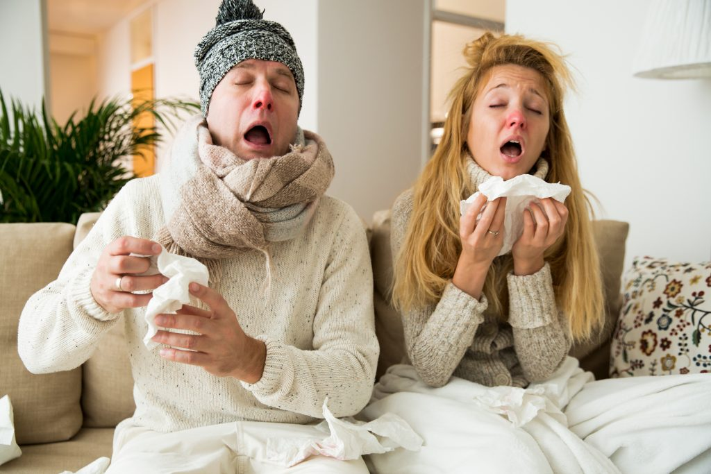 Sick couple catch cold. Man and woman sneezing,